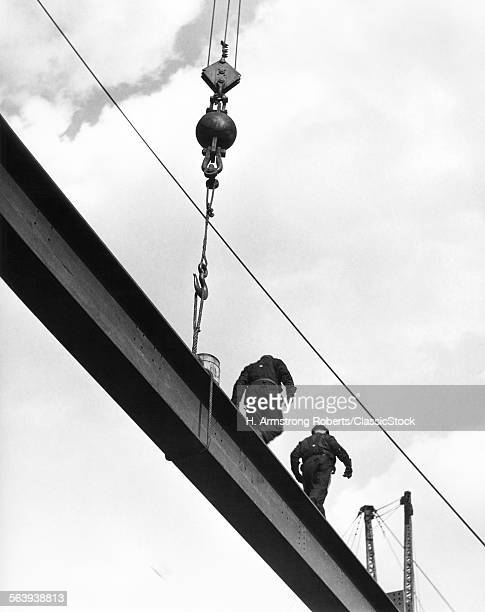 1930s TWO ANONYMOUS MEN CONSTRUCTION WORKERS WALK ALONG LENGTH OF STEEL I BEAM