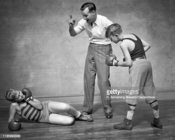 1930s TWO BOYS SPARRING PUNCHING BOXING ONE BOY KNOCKED DOWN MAN ACTING AS REFEREE COUNTING HIM OUT