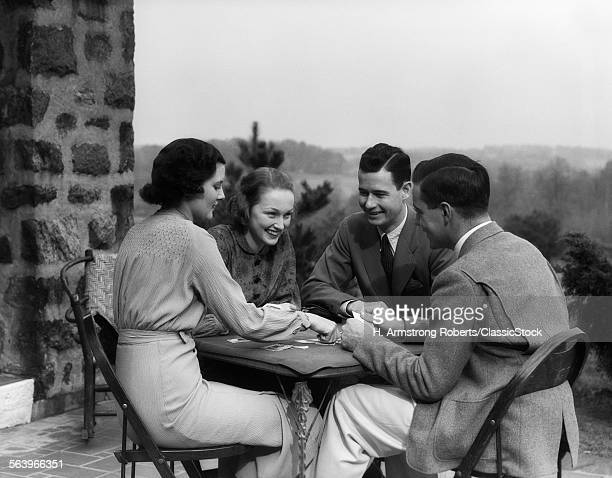 1930s TWO COUPLES PLAYING CARDS AT TABLE ON OUTDOOR PATIO