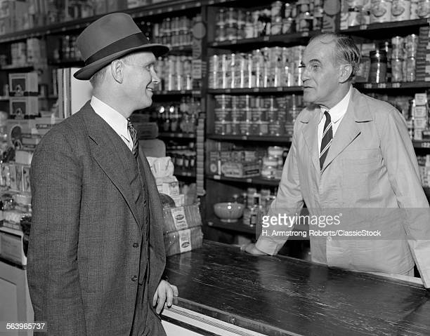 1930s TWO MEN CLERK AND CUSTOMER TALKING OVER COUNTER IN RETAIL GENERAL STORE