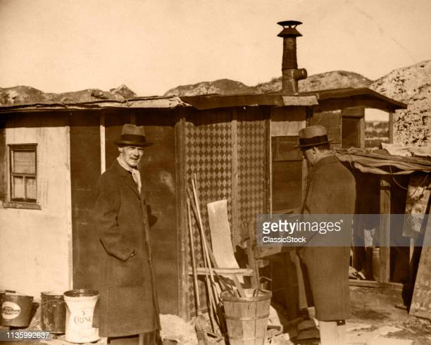1930s TWO MEN IN HATS AND OVERCOATS STANDING BY HOOVERVILLE SHANTY TOWN TRAILER PARK DEPRESSION VILLAGE VARIOUS CITIES USA