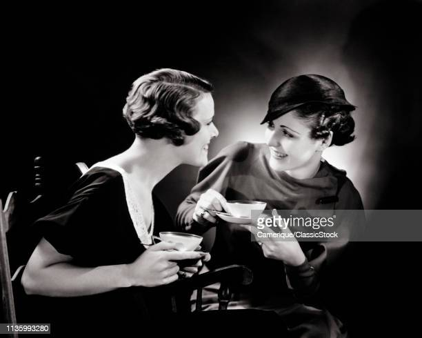 1930s TWO SMILING WOMEN SITTING TOGETHER DRINKING TEA TALKING AND GOSSIPING