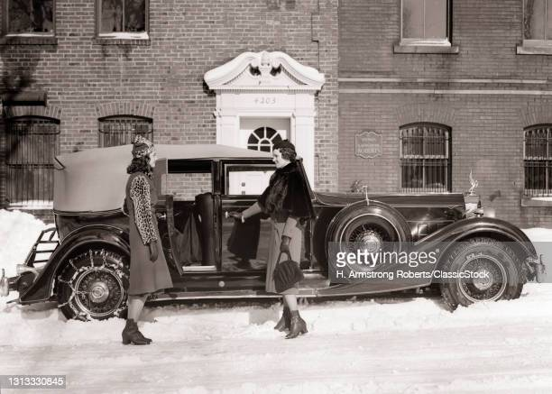 1930s Woman And Teen Girl Entering Packard Touring Car Equipped With Chains On Rear Tires Parked On Winter Snow Covered Street.