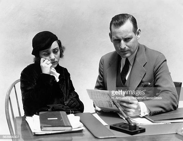 1930s WOMAN CRYING WITH TISSUE MAN SITTING AT DESK