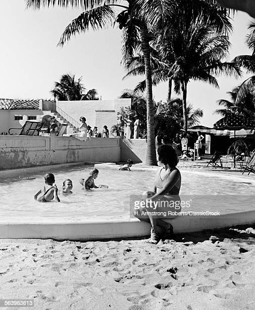 1930s WOMAN WATCHING CHILDREN PLAYING IN KIDDY POOL