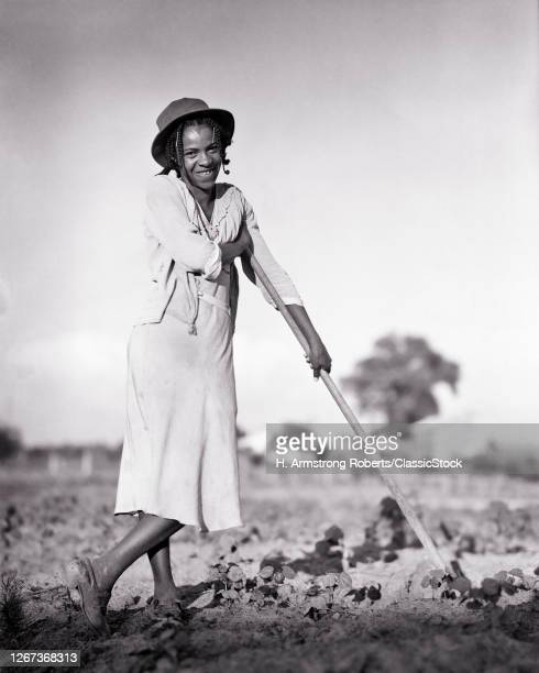 1930s Young African-American Woman Braided Hair Wearing Old Hat Leaning On Hoe Looking At Camera Tobacco Farm North Carolina USA