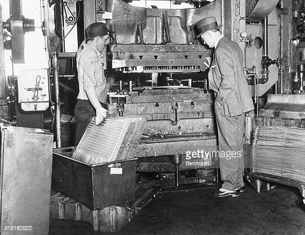 C E Allen Commercial VicePresident of the Westinghouse Electric and Manufacturing Company is shown inspecting a punch press which is used in the...