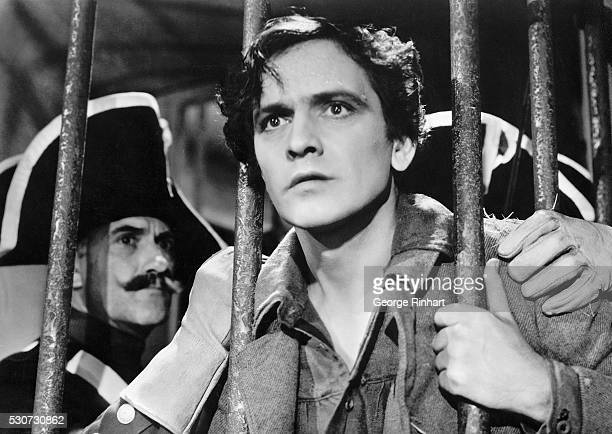 1935Movie still from 'Les Miserables' Photo shows a prison scene with Frederic March holding on to prison bars as lawmen have their grasp on him...