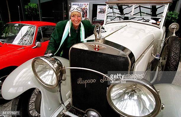 1937Rallyefahrerin Autohändlerin D posiert mit Rennkappe vor dem Start zur2000 km Fahrt durch Deutschland mitzwei Oldtimern rechts ein weisserHispano...