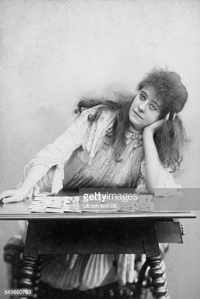 1864 1937Schauspielerin DHalbfigur an einem Tisch mit Spielkarten 1895Fotografie von KuK HofAtelier Adele