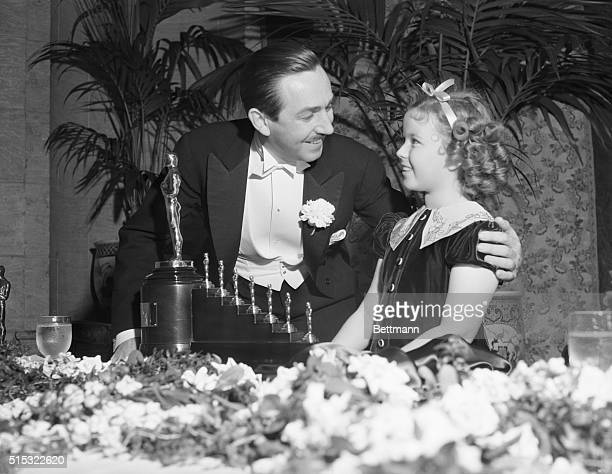 1939Los Angeles CA Shirley Temple presents an Academy Award to Walt Disney for his outstanding cartoon Snow White and the Seven Dwarfs one big statue...