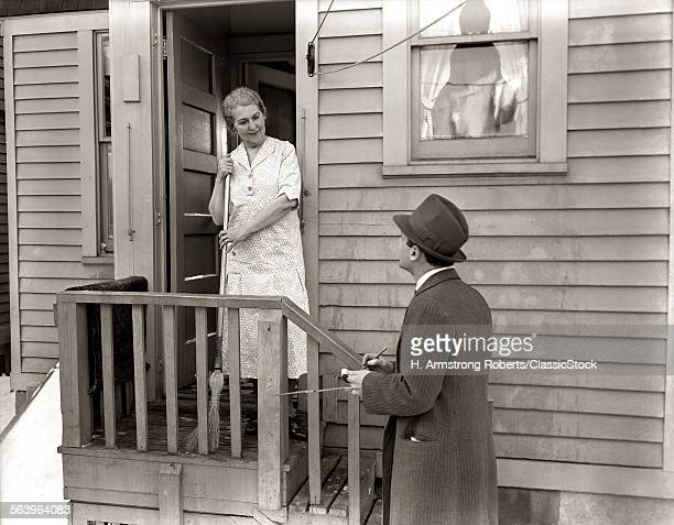 1940s 1930s MAN DOORTODOOR SALESMAN TALKING WOMAN TO HOUSEWIFE AT BACK DOOR