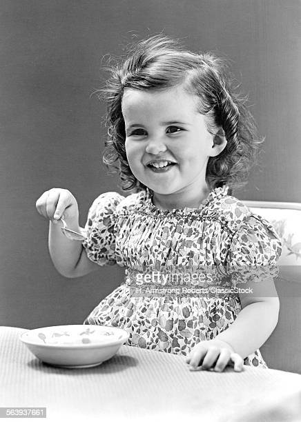 1940s 1930s SMILING LITTLE GIRL EATING BOWL OF ICE CREAM