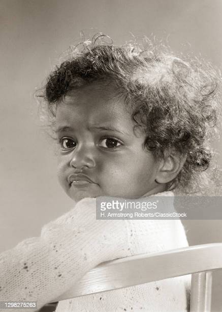1940s 1950s African American Baby Girl Sitting Up In Chair Looking Over Her Shoulder Big Eyes Curly Hair.