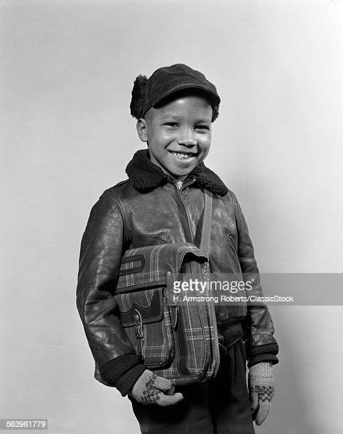 1940s 1950s AFRICAN AMERICAN BOY SMILING WEARING WINTER JACKET GLOVES HOLDING SCHOOL BOOK BAG