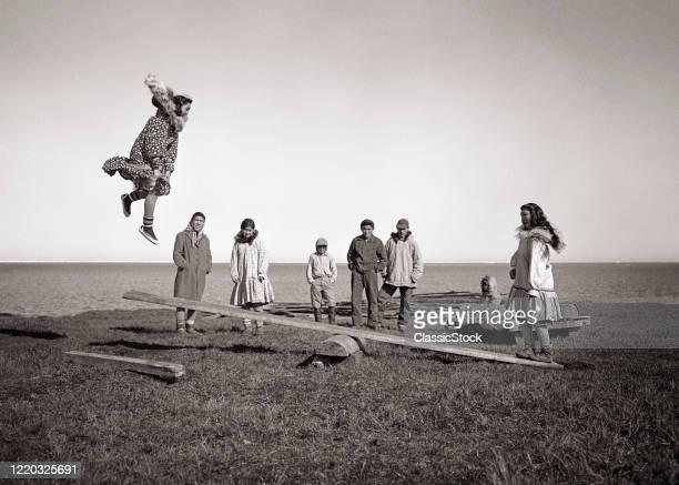 1940s 1950s alaskan eskimo children and teens playing a game of jumpboard a kind of seesaw game arctic kotzebue alaska USA
