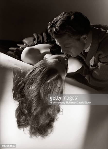 1940s 1950s ANONYMOUS SILHOUETTED ROMANTIC COUPLE EMBRACING ABOUT TO KISS SITTING ON SOFA