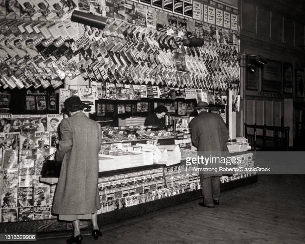1940s 1950s Anonymous Woman And Man Looking At Selecting Purchasing Publications Books And Newspapers At Well Stocked Newsstand.