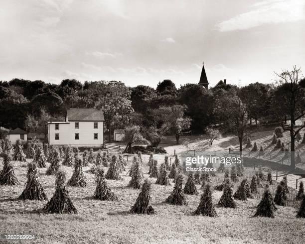 1940s 1950s Autumn Farm Scene Farmhouse With Field Of Corn Shocks Church Spire On Horizon Lancaster County Pennsylvania USA