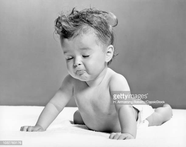 1940s 1950s BABY LYING ON STOMACH LEANING ON HANDS EYES CLOSED