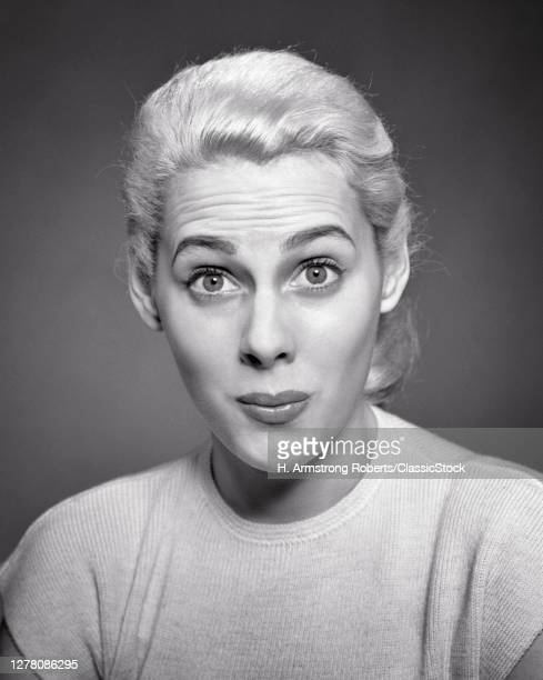 1940s 1950s Blond Young Woman Wearing White T-Shirt Looking At Camera Directly With Wide-Eyed Surprised Facial Look