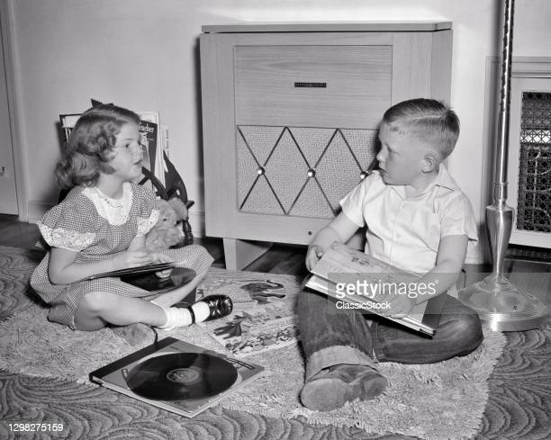 1940s 1950s Boy And Girl Brother Sister Sitting Before Record Player Phonograph Listening To Music Playing Records.