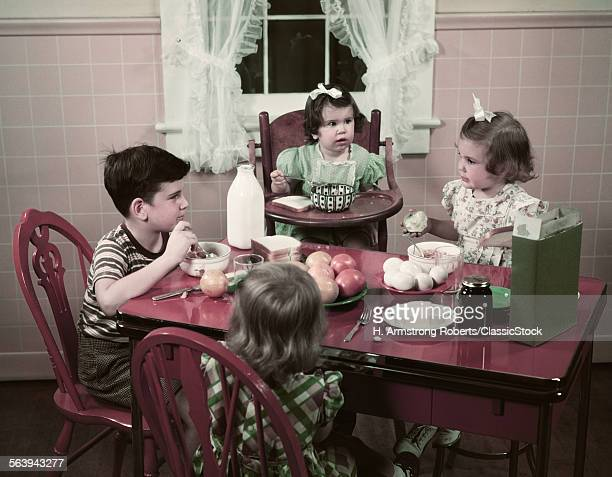 1940s 1950s BOY AND GIRLS EATING BREAKFAST AT KITCHEN TABLE FOOD CEREAL BREAD MILK EGGS APPLES