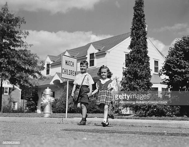 1940s 1950s BOY GIRL HOLDING HANDS CROSSING STREET GOING TO SCHOOL WATCH CHILDREN SIGN