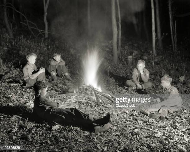 1940s 1950s Boy Scout Troop Sitting Around Campfire At Night.