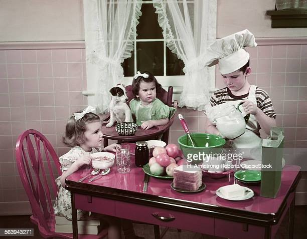 1940s 1950s BOY TWO GIRLS AT KITCHEN TABLE BOY IN TOQUE COOKING ONE GIRL EATING TODDLER AND PUPPY IN HIGH CHAIR