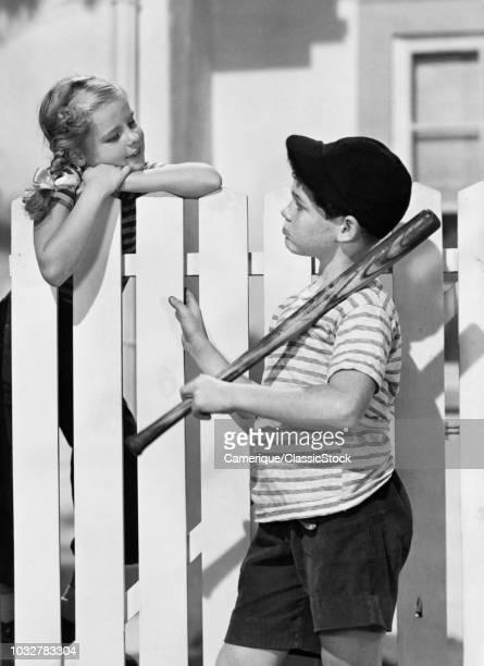 1940s 1950s BOY BASEBALL BAT CAP TALKING TO GIRL OVER WHITE PICKET FENCE