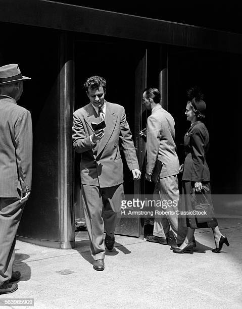 1940s 1950s BUSINESS MEN AND WOMAN ENTERING AND LEAVING BUILDING