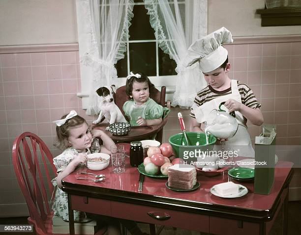 1940s 1950s CHILDREN TWO GIRLS AT KITCHEN TABLE WITH PUPPY AND BOY COOKING WEARING CHEFS TOQUE