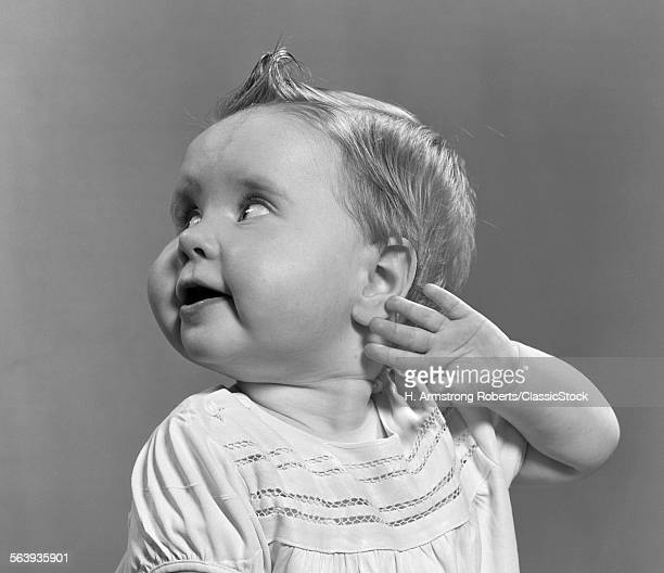1940s 1950s CLOSEUP PORTRAIT OF BABY GIRL WITH CURL ON TOP OF HEAD LOOKING TO SIDE WITH HAND HELD UP BESIDE EAR