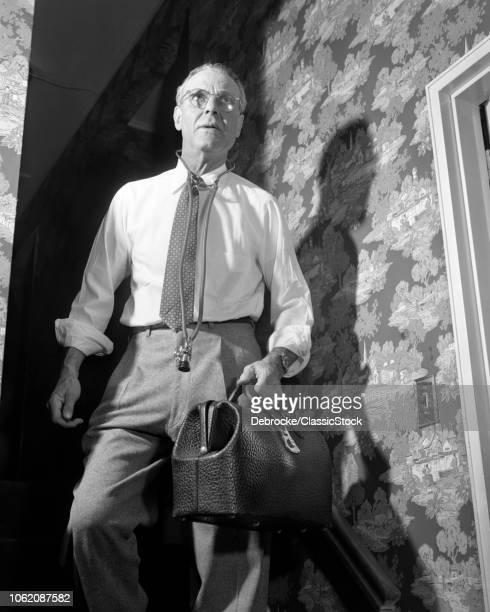 1940s 1950s DOCTOR WITH BAG AND STETHOSCOPE WALKING DOWN STAIRS IN HOME AFTER MAKING AN EMERGENCY HOUSE CALL