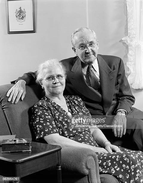 1940s 1950s ELDERLY COUPLE SITTING ON COUCH SMILING LOOKING AT CAMERA