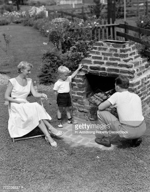 1940s 1950s FAMILY IN BACKYARD COOKING HAMBURGERS ON BRICK BARBECUE