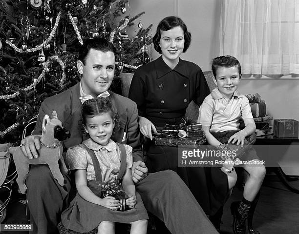 1940s 1950s FAMILY SITTING AROUND CHRISTMAS TREE HOLDING GIFTS LOOKING AT CAMERA