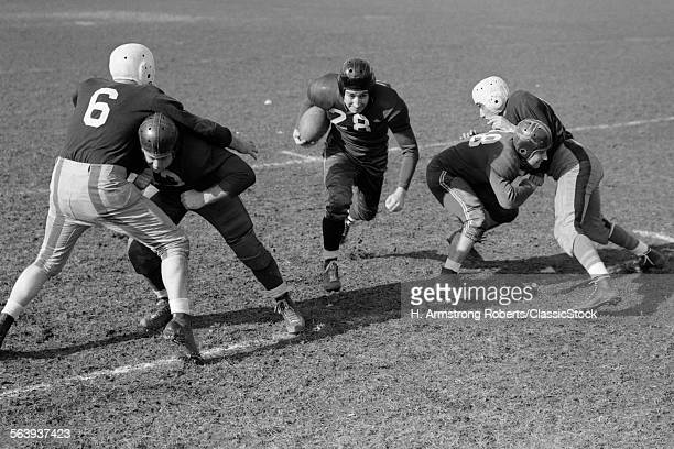 1940s 1950s FOOTBALL PLAYER RUNNING WITH BALL AS BLOCKERS DEFEND HIM