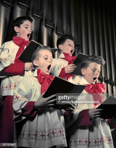 1940s 1950s FOUR CHOIR BOYS IN RED AND WHITE ROBES SINGING IN FRONT OF CHURCH ORGAN PIPES