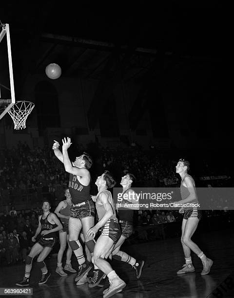 1940s 1950s HIGH SCHOOL BASKETBALL GAME INDOORS JUMP SHOT BALL JUST THROWN ABOUT TO GO IN BASKET