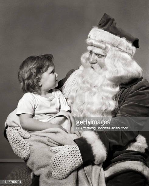 1940s 1950s LITTLE GIRL SITTING ON SANTA CLAUS LAP SMILING AT EACH OTHER