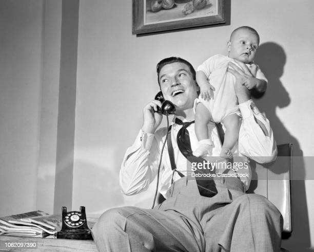 1940s 1950s MAN FATHER TALKING ON TELEPHONE HOLDING BABY BOY UP WITH ONE HAND