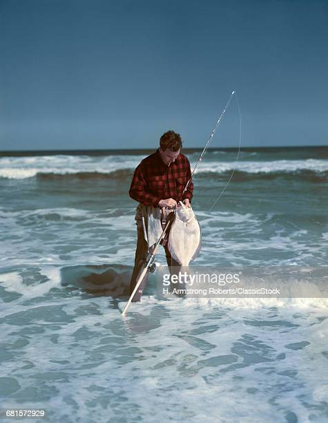 1940s 1950s MAN FISHING WEARING RED BLACK CHECKED SHIRT STANDING IN OCEAN SURF REMOVING FLOUNDER FROM HOOK