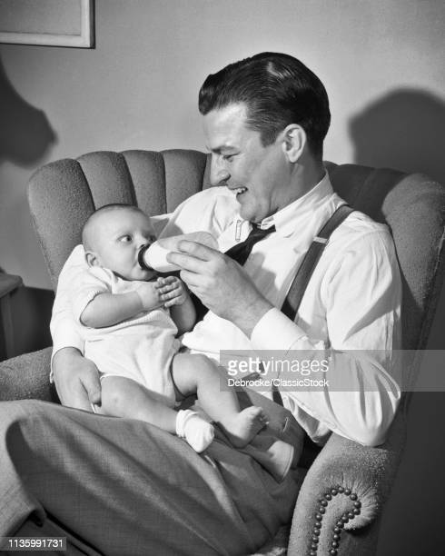 1940s 1950s MAN SMILING FATHER SITTING IN LIVING ROOM CHAIR HOLDING AND MILK BOTTLE FEEDING BABY BOY SON
