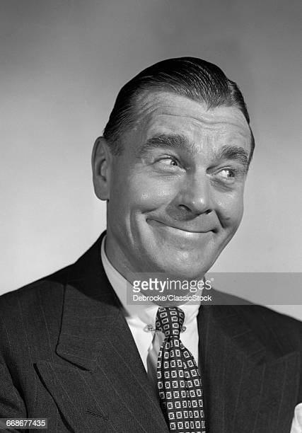 1940s 1950s MAN SMILING BUSINESSMAN WITH FUNNY AMUSED FACIAL EXPRESSION LOOKING OFF TO SIDE