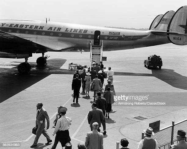 1940s 1950s PASSENGERS BOARDING EASTERN AIR LINES PROPELLER LOCKHEED CONSTELLATION AIRPLANE STANDING ON AIRPORT TARMAC