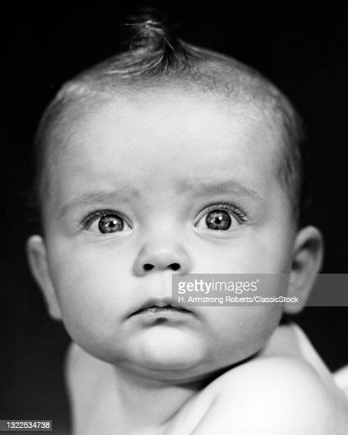 1940s 1950s Portrait Baby Girl Serious Sincere Facial Expression Intense Focused Looking At Camera.