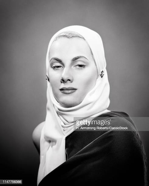 1940s 1950s PORTRAIT HANDSOME BLONDE WOMAN WEARING WHITE HEAD SCARF EYES CAST ASIDE WITH LOOK OF SADNESS OR DISDAIN