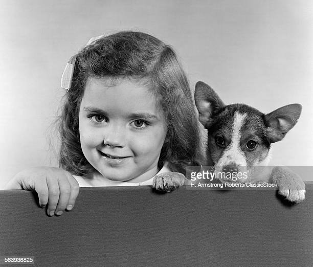 1940s 1950s PORTRAIT OF LITTLE GIRL WITH SMALL DOG LOOKING AT CAMERA